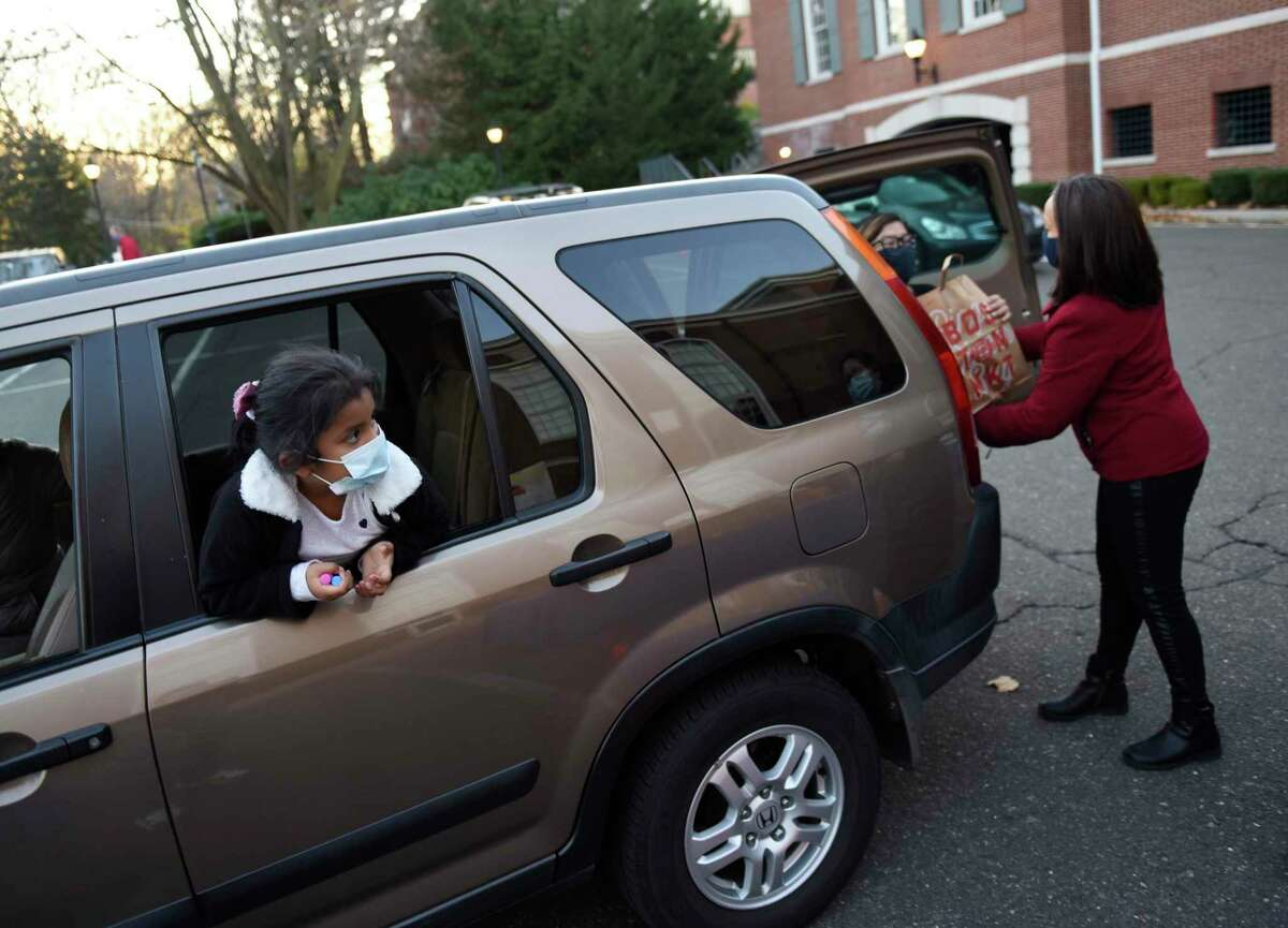 Club members pick up Thanksgiving meals at the Boys & Girls Club in Greenwich, Conn. Tuesday, Nov. 24, 2020. The Club usually feeds 400 kids but scaled down the event due to public health needs.