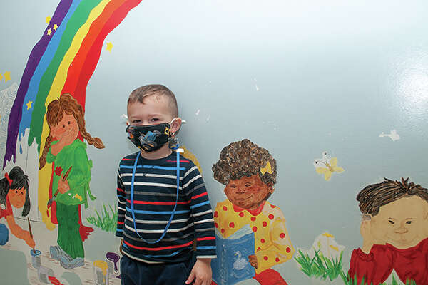 Dax McGillicuddy, 3, stands Tuesday morning by the rainbow mural at Bright Beginnings Child Care. Dax said he is thankful for bacon as Thanksgiving Day approaches.