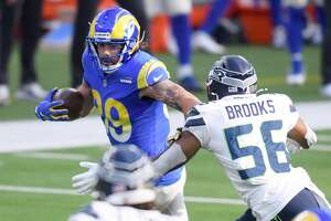 INGLEWOOD, CALIFORNIA - NOVEMBER 15: Tyler Higbee #89 of the Los Angeles Rams carries the ball against Jordyn Brooks #56 of the Seattle Seahawks in the first quarter at SoFi Stadium on November 15, 2020 in Inglewood, California. (Photo by Harry How/Getty Images)