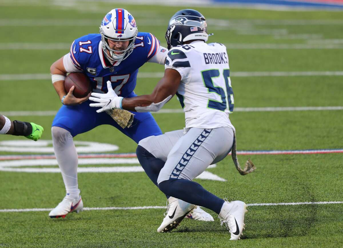 ORCHARD PARK, NEW YORK - NOVEMBER 08: Josh Allen #17 of the Buffalo Bills carries the ball as Jordyn Brooks #56 of the Seattle Seahawks defends during the second half at Bills Stadium on November 08, 2020 in Orchard Park, New York. (Photo by Timothy T Ludwig/Getty Images)