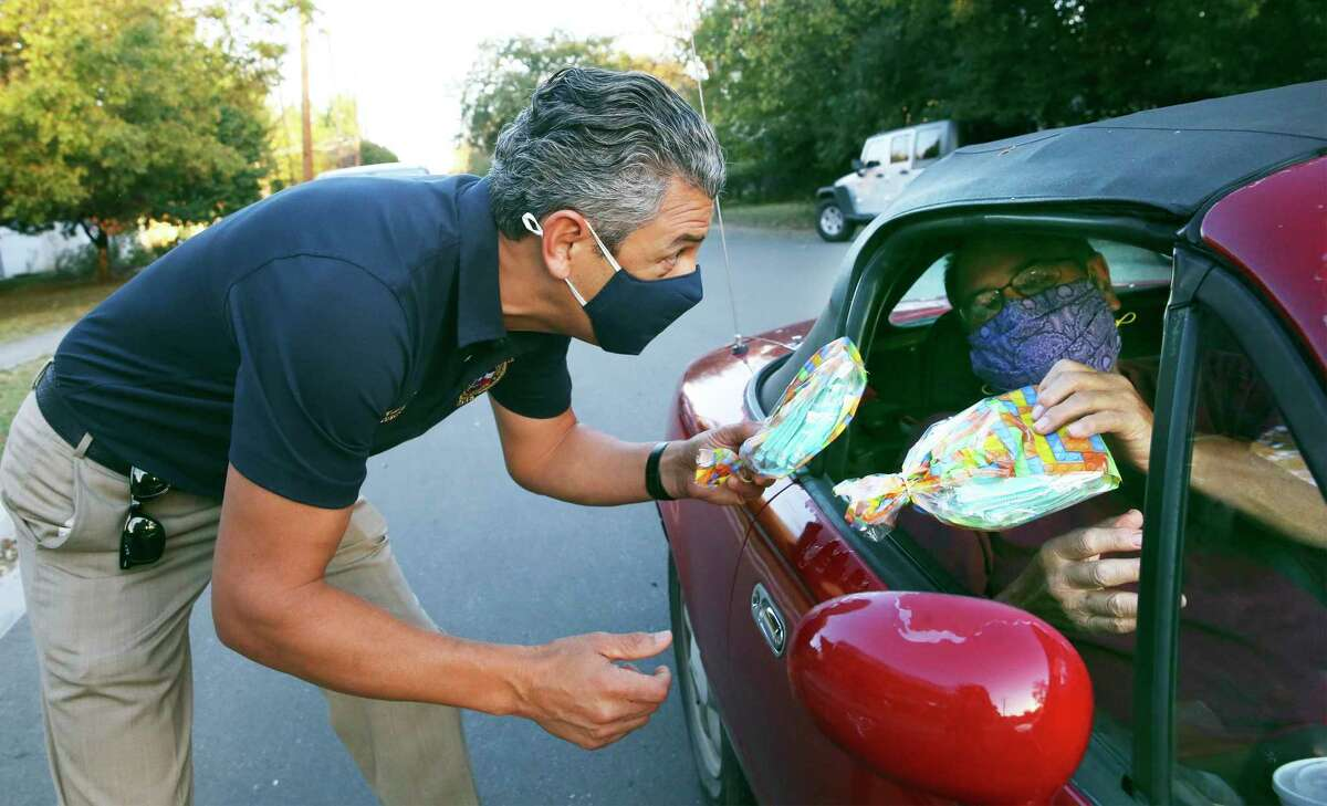 Hays County Judge Ruben Becerra, left, along with Emergency Management Coordinator Alex Villalobos hand out some of the 5,000 N95 masks to motorists and walk ups at the Centro Cultural Hispano de San Marcos on Nov. 18, 2020