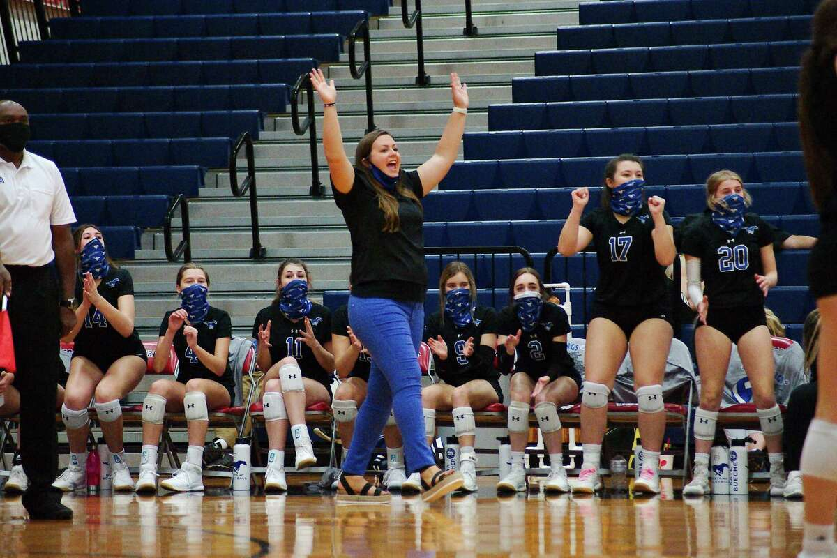 Friendswood volleyball coach Sarah Paulk and the Lady Mustangs celebrate a point against Terry Tuesday, Nov. 24 at Manvel High School.