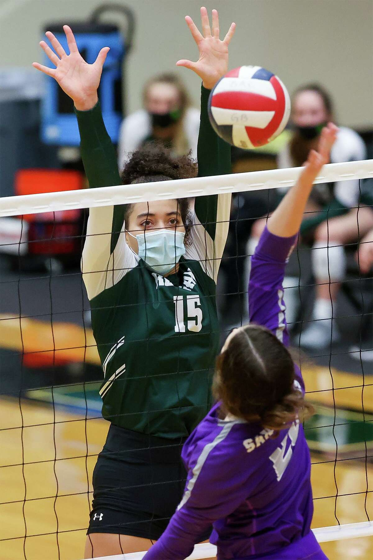 Reagan's Nyah Anderson looks to block a shot by San Marcos' Samantha Booth during their Class 6A volleyball second-round playoff match at Littleton Gym on Tuesday, Nov. 23, 2020. Reagan won the match in three sets: 25-20, 25-13, 25-12.