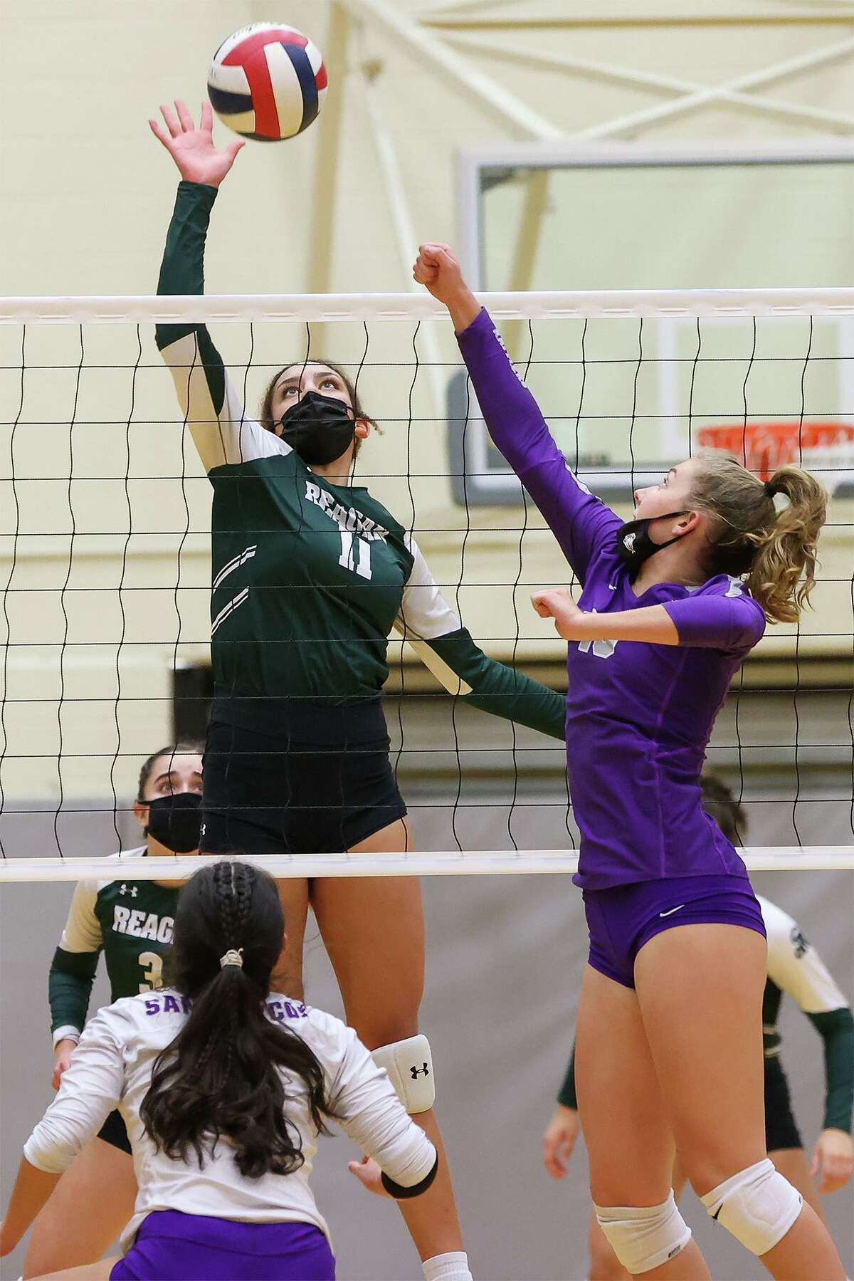 Reagan's Preslie Yates, left, looks to score over San Marcos' Emery Jones, right, during their Class 6A volleyball second-round playoff match with San Marcos at Littleton Gym on Tuesday, Nov. 23, 2020. Reagan won the match in three sets: 25-20, 25-13, 25-12.