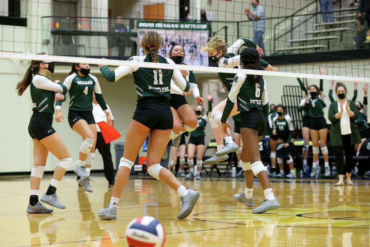 The Reagan Lady Rattlers celebrate the final point in their victory over San Marcos in their Class 6A volleyball second-round playoff match at Littleton Gym on Tuesday, Nov. 23, 2020. Reagan won the match in three sets: 25-20, 25-13, 25-12.