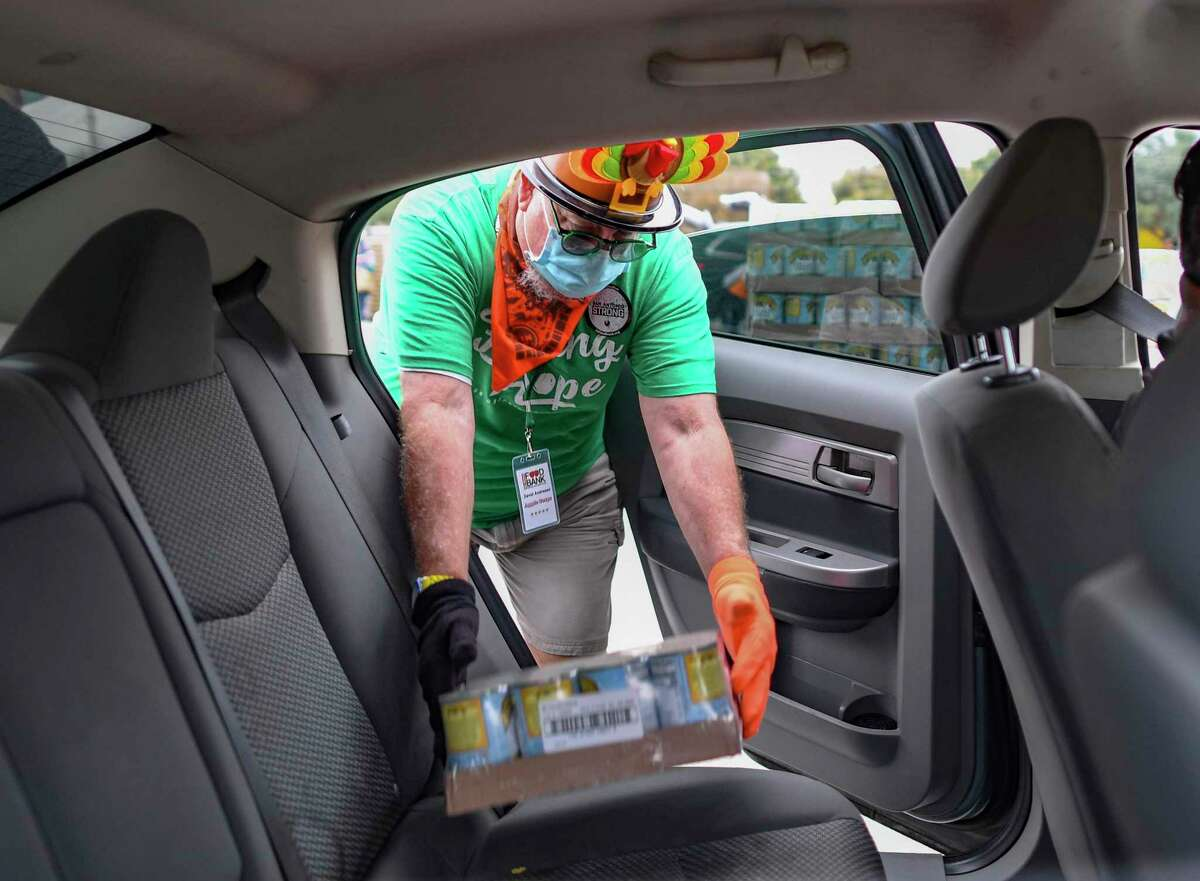 David Andersen, clad in Thanksgiving holiday garb, loads collard greens into a vehicle at the Alamodome. More than 2,000 families received food from the San Antonio Food Bank on Tuesday morning, Nov. 24, 2020. The lines aren't as long as they were at Traders Village in April shortly after the coronavirus pandemic hit San Antonio, but the need is the same. The number of events has increased to make lines shorter.