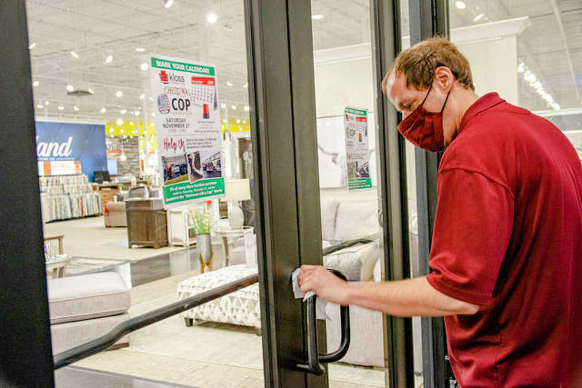 Todd, a warehouseman at Kloss Furniture Store in Edwardsville, sanitizes the front doors Tuesday afternoon.