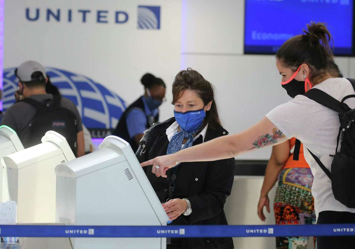 A United Airlines employee assists a departing passenger at Los Angeles International Airport (LAX) on October 1, 2020 in Los Angeles.
