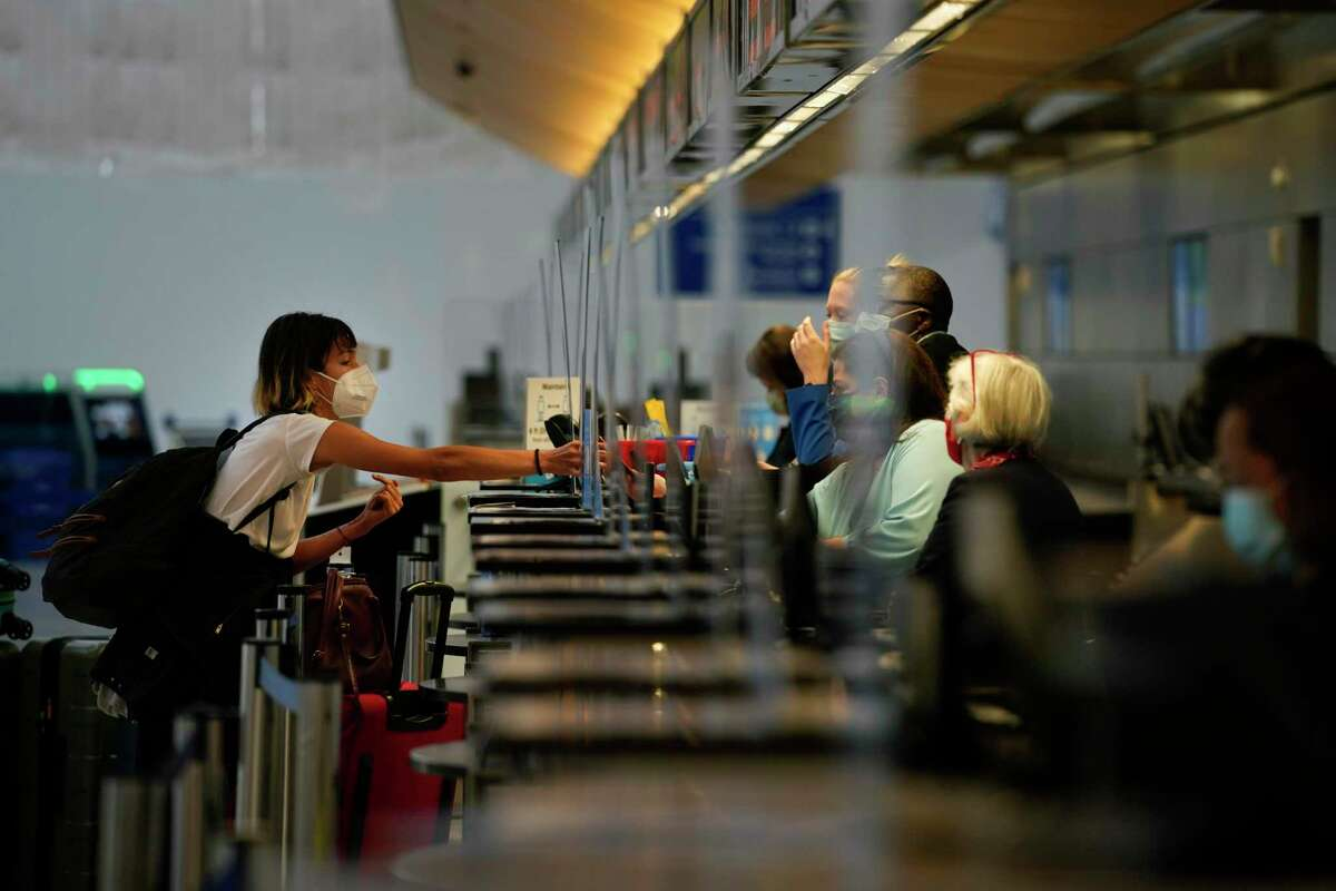 A woman checks in for her flight at the Los Angeles International Airport in Los Angeles, Monday, Nov. 23, 2020. About 1 million Americans a day packed airports and planes over the weekend even as coronavirus deaths surged across the U.S. and public health experts begged people to stay home and avoid big Thanksgiving gatherings.
