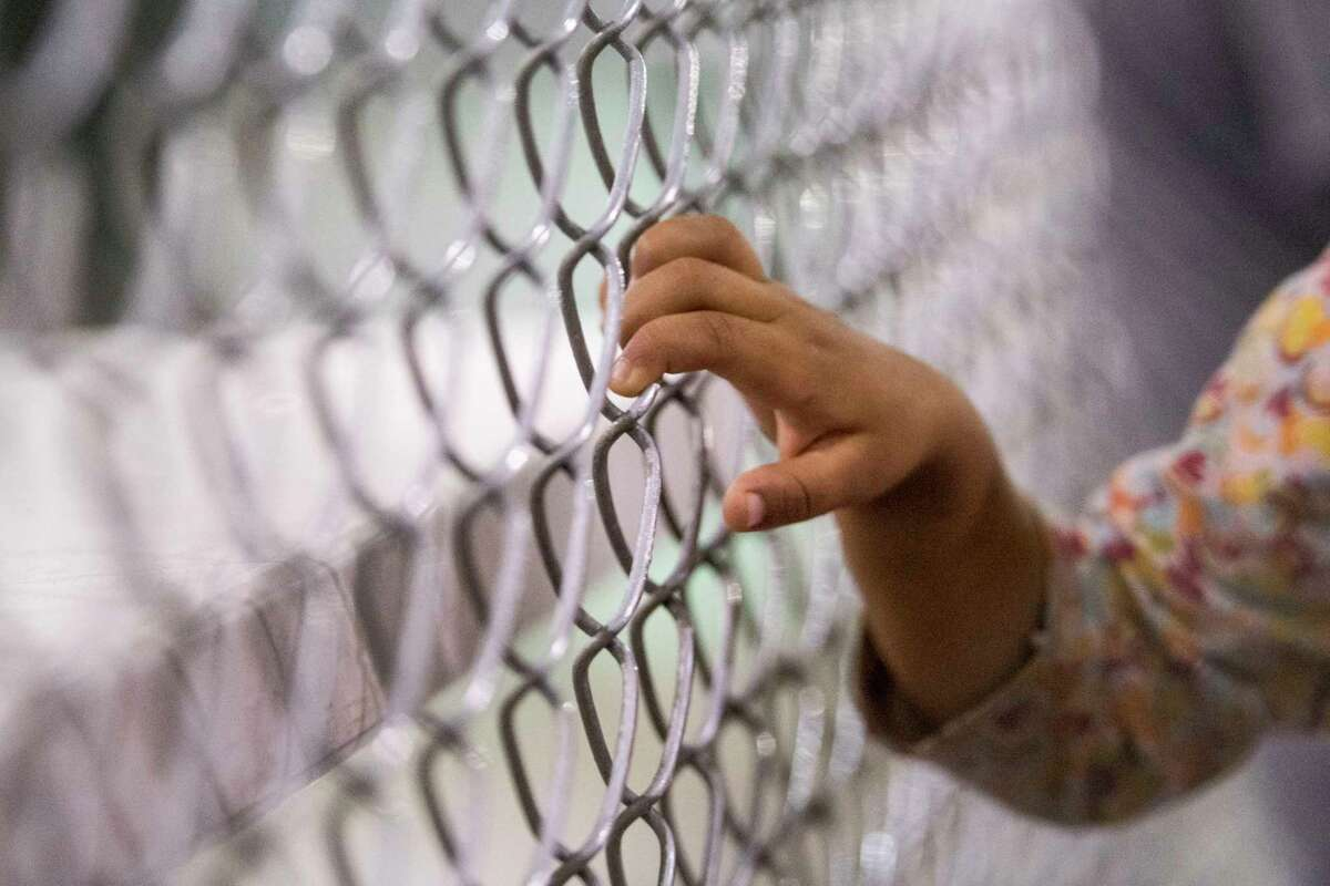 A young child holds onto a fence at the U.S. Border Patrol Central Processing Center in McAllen, Tex., in August 2019.