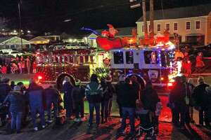 A decorated fire truck drives through town during a past Holiday Light Parade in New Fairfield, Conn.
