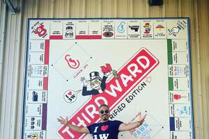Marc Newsome poses in front of his lastest installation, a Third Ward gentrification Monopoly Board.