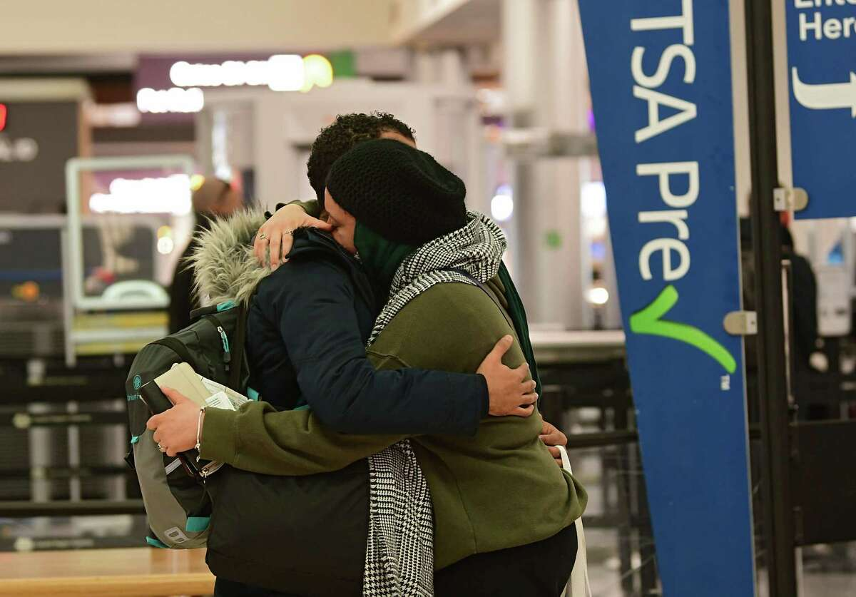 Enmanuel Castellanos of Schenectady, left, gives his girlfriend Hannah S a hug before she boards her plane for Charlotte, N.C. for the Thanksgiving holiday at the Albany International Airport on Tuesday, Nov. 24, 2020 in Colonie, N.Y. The Times Union wants to hear your stories of reunion now that vaccination is making people more comfortable with travel after the pandemic began in March 2020. (Lori Van Buren/Times Union)