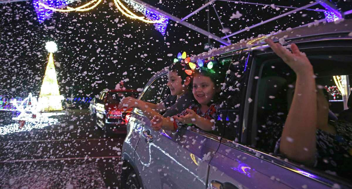 Luis Herrera, 7, and his sister, Haley, 5, enjoy illumiNight: A Magical Drive-Thru Experience at the AT&T Center.
