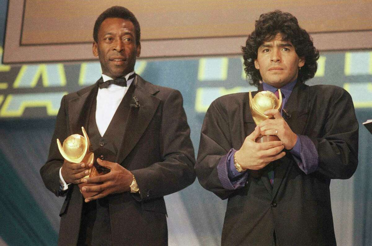 """FILE - In this March 1987 file photo, Pele, left, and Maradona hold """"Sports Oscar"""" trophies in Milan, Rome. The Argentine soccer great who was among the best players ever and who led his country to the 1986 World Cup title before later struggling with cocaine use and obesity, died from a heart attack on Wednesday, Nov. 25, 2020, at his home in Buenos Aires. He was 60."""