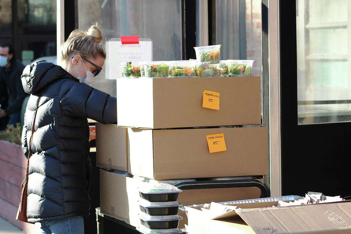 Emily Bugg helps package Thanksgiving meals for delivery to Thresholds clients.