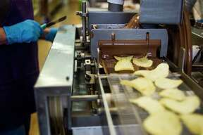 Aaron Gallagher and Kim Suttle work to coat potato chips in chocolate Tuesday morning inside Heather N' Holly in Midland. (Katy Kildee/kkildee@mdn.net)