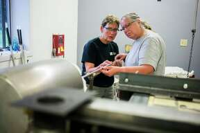Glass blowing instructor Debra VanTol, left, assists Wendy Gilbert of St. Charles, right, heat molten glass during the second session of a four-week glass blowing class Wednesday, Oct. 2, 2019 at Village Glass Works in Auburn. (Katy Kildee/kkildee@mdn.net)