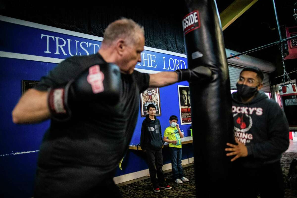 Isaac Chmiel, 13, and his brother Francisco, 9, watch their adoptive father Michael Chmiel, left, train at Rocky's Boxing Gym at 1524 Freeman.