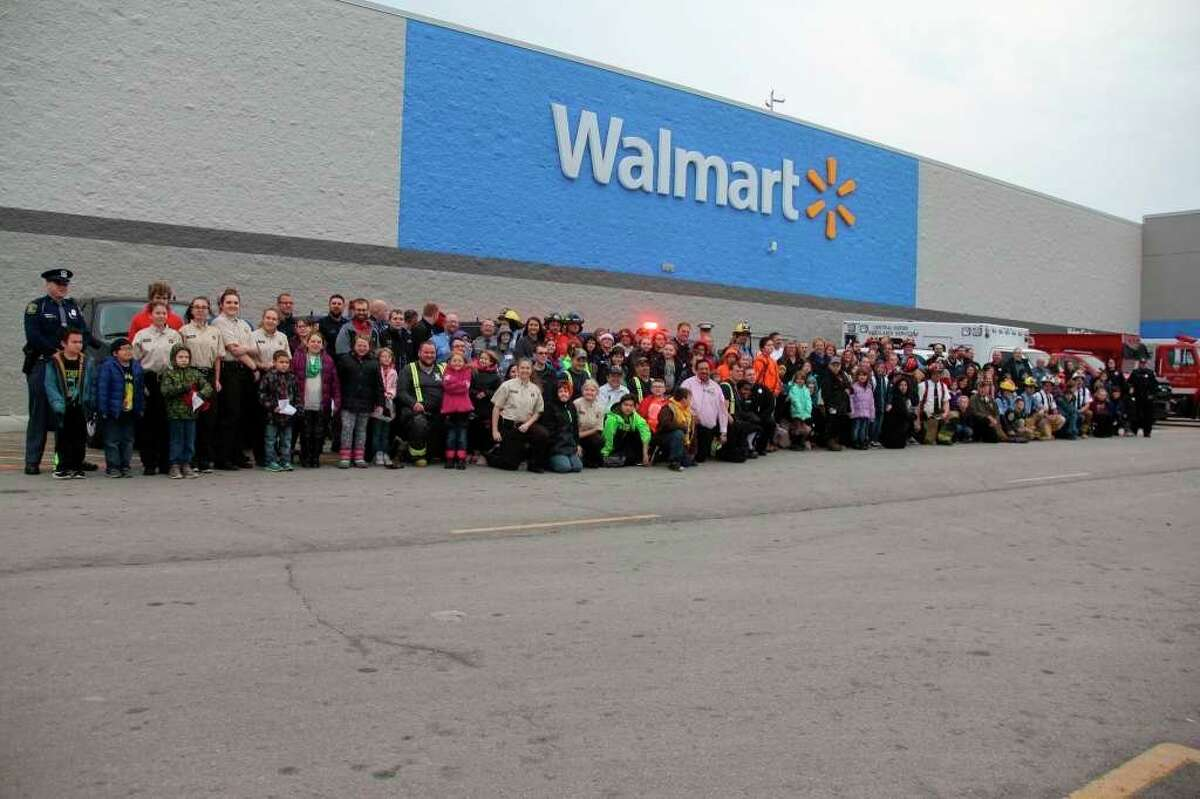 Heros and participants pose for a photo in front of Walmart during a previous Shop With a Hero event. This year's event will see some changes due to the coronavirus pandemic. (Tribune File Photo)