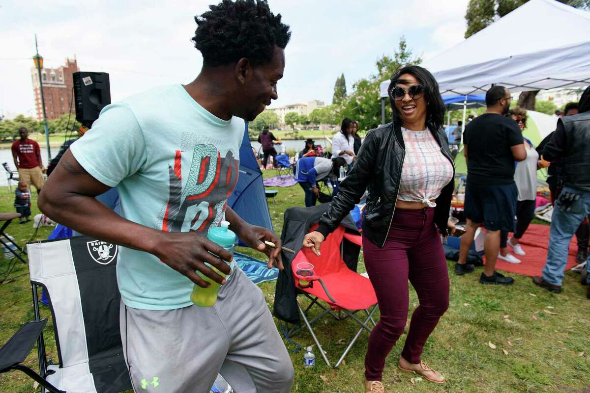 """Kali Wilson, left, and Gayla Thompson dance together during the """"BBQ'n While Black"""" party at Lake Merritt in Oakland, CA, on Sunday May 20, 2018."""