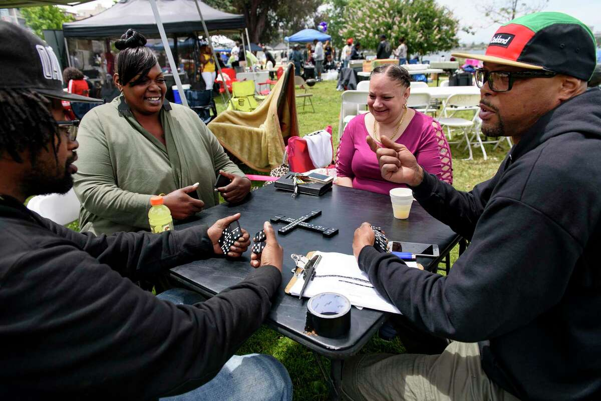 """James Curtis, left, Kesha Mary, Angelic Edwards and Jovan Smith play dominos during the """"BBQ'n While Black"""" party at Lake Merritt in Oakland, CA, on Sunday May 20, 2018."""