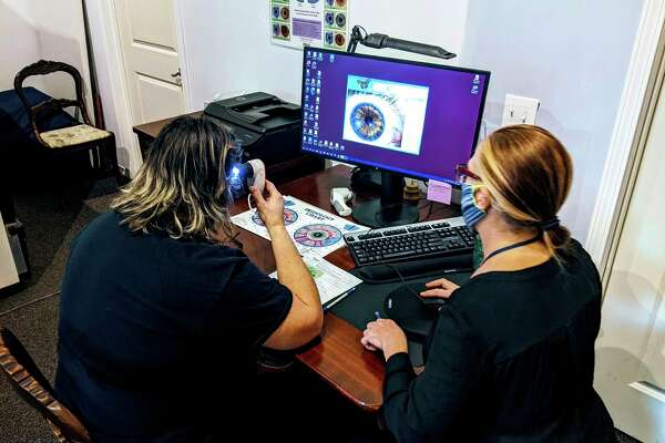 Shannon Scruggs-Allen, right, who owns Metamorphosis Holistic Health LLC in Cass City, is doing an iridology/health assessment to a client. (Aaron Rodrigez/Courtesy Photo)