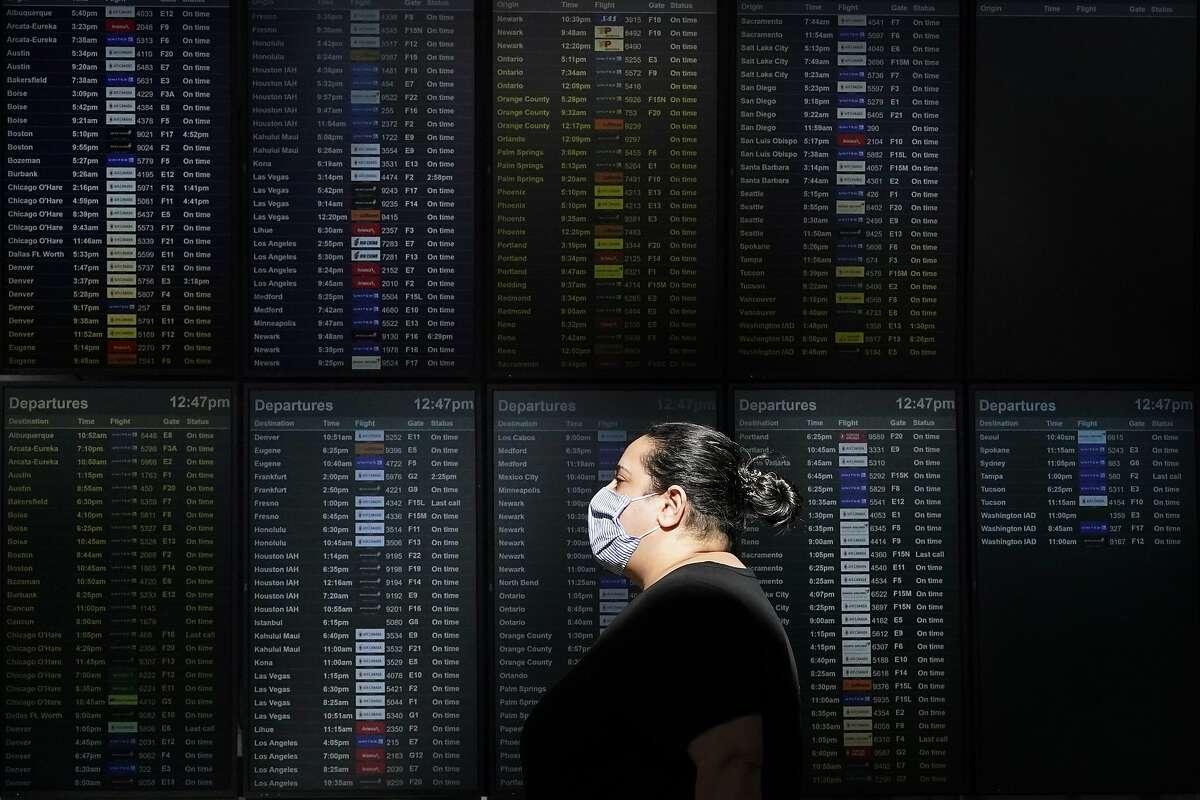 A woman walks past a flight information board at San Francisco International Airport.