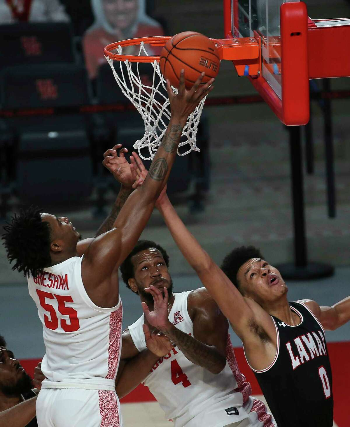 Houston Cougars forward Brison Gresham (55) puts a rebound into the basket wihle Lamar Cardinals center David Muoka (0) is tyring to stop him during the first half of a American Athletic Conference game Wednesday, Nov. 25, 2020, at Fertitta Center in Houston.
