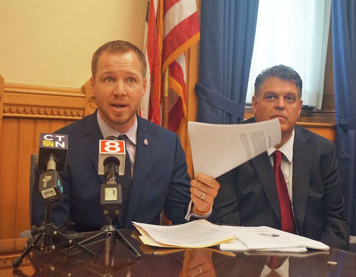 Scott Dolch (left), executive director of the Connecticut Restaurant Association, brandished a document that he said contained incorrect guidance from the Department of Labor on state wage regulations. He was joined by Rep. David Rutigliano (right), R-Trumbull, at a press conference at the state Capitol in Hartford, Conn. on Friday July 19, 2019.