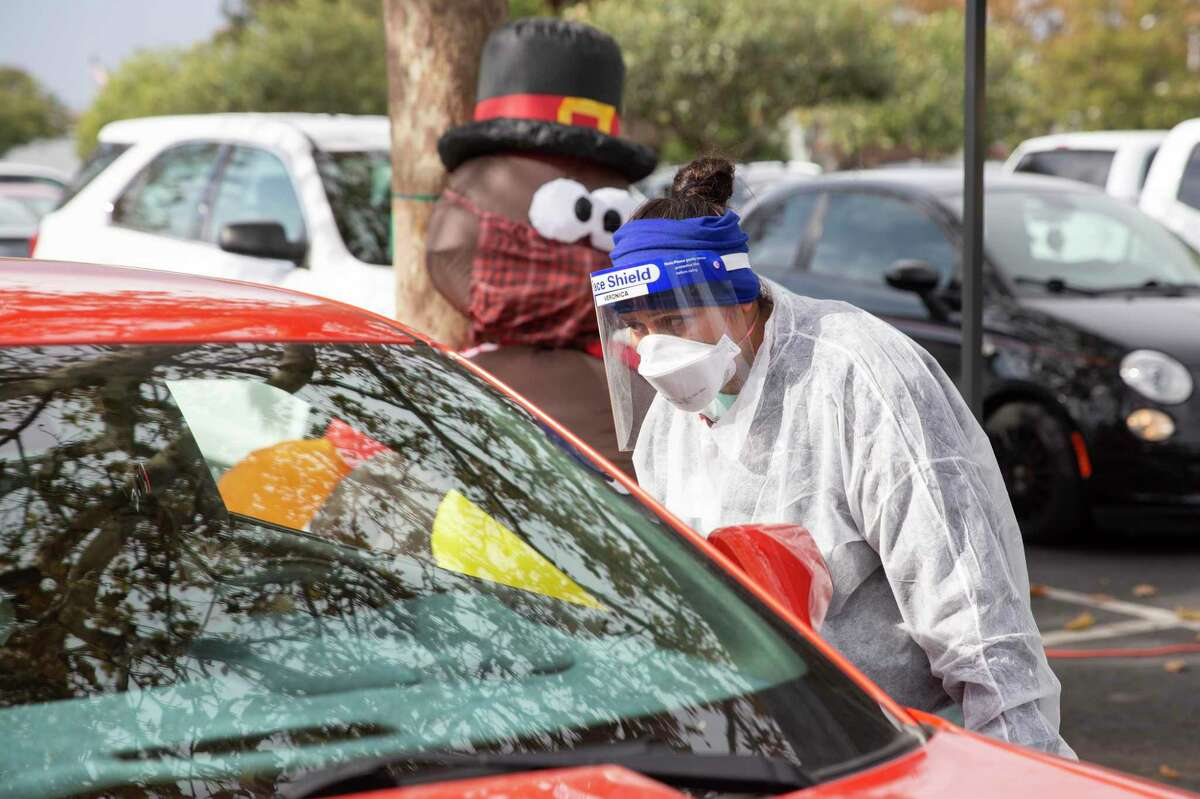 A woman in California prepares to test a family for COVID-19 in advance of Thanksgiving. On this holiday, which is all about gratitude and being with family, make smart decisions to keep your loved ones safe.