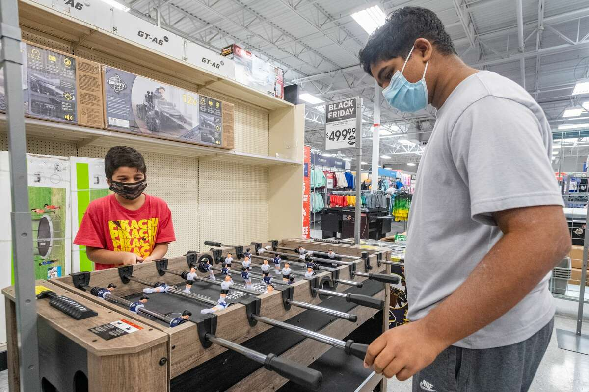 Narad Rampersad, 9, and Narayan Rampersad, 14, play a little foosball while their parents shop. Shoppers were out taking advantage of the early Black Friday deals Wednesday at Academy Sports + Outdoors in Beaumont. Photo made on November 25, 2020. Fran Ruchalski/The Enterprise