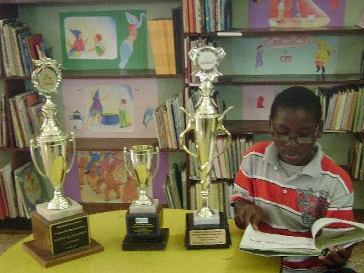 Fitzroy Wickham reading as a young boy at a local library in Brown's Town, Jamaica.