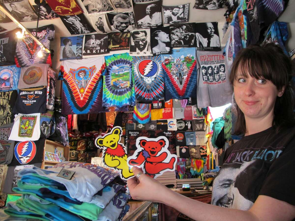 Greta Marti, co-owner of Haight Ashbury T-Shirts, holds up stickers of the Grateful Dead's marching bears at her family's shop on July 1, 2015. The 43-year-old shop will close at the end of December due to the pandemic and lack of foot traffic in the area.