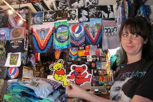 FILE - Greta Marti, co-owner of Haight Ashbury T-Shirts, holds up stickers of the Grateful Dead's marching bears at her family's shop on July 1, 2015. The 43-year-old shop will close at the end of December due to the pandemic and lack of foot traffic in the area.