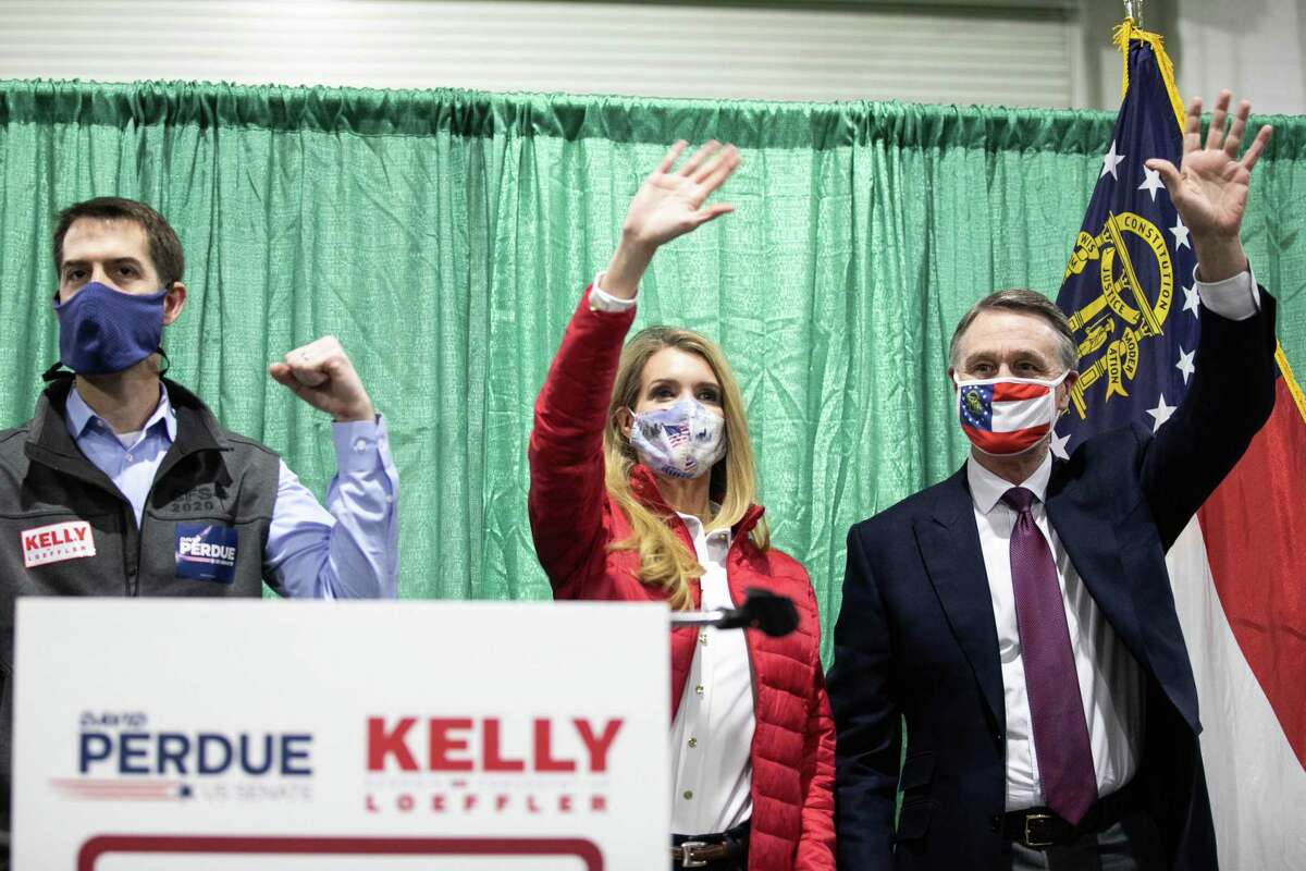 PERRY, GA - NOVEMBER 19: (R to L) U.S. Sen. David Purdue (R-GA) and Sen. Kelly Loeffler (R-GA) wave to the crowd of supporters at a
