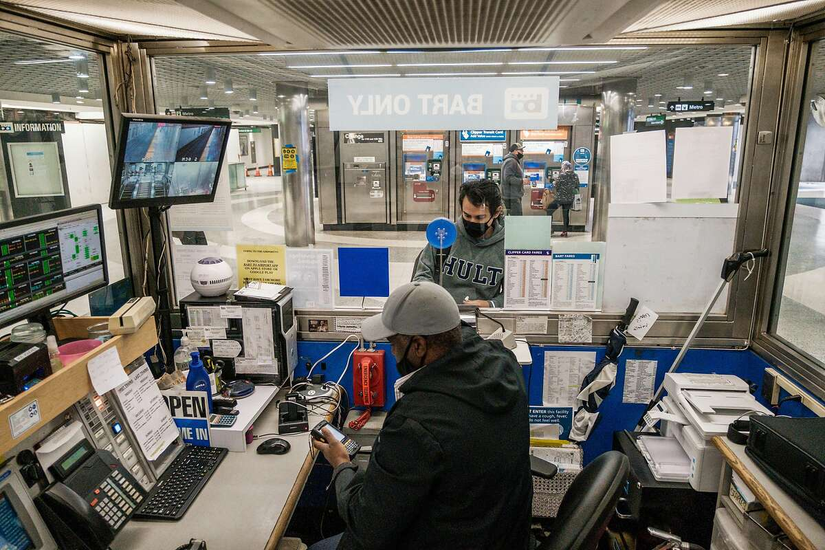 Derek Mccullum, a Bart station agent, helps a passenger at the Powell Street Station in San Francisco on Wednesday, November 25, 2020.