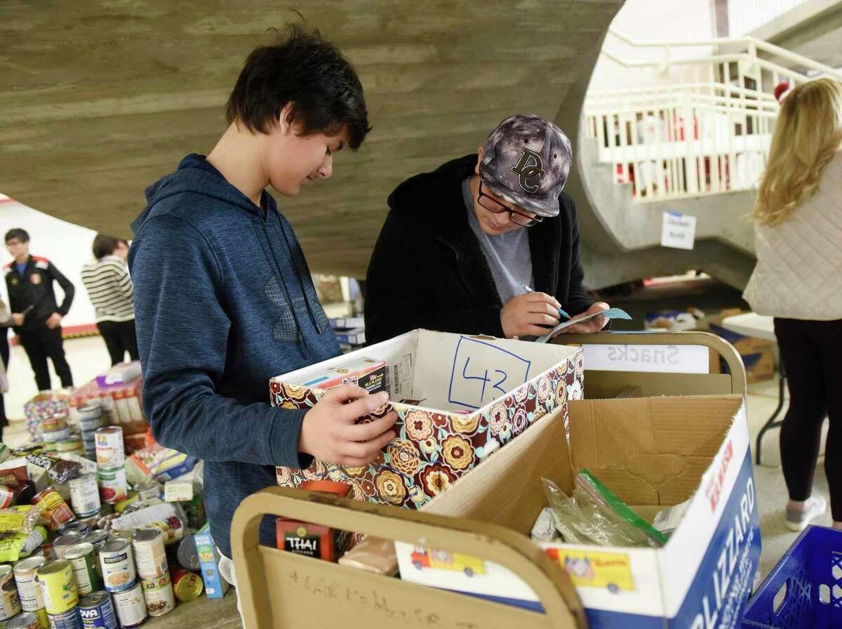 Two students last year organize donated Thanksgiving meals for the GHS Roots & Shoots Club Thanksgiving Food Drive at Greenwich High School on Nov. 25, 2019. This year, the food drive was virtual and raised $20,000.