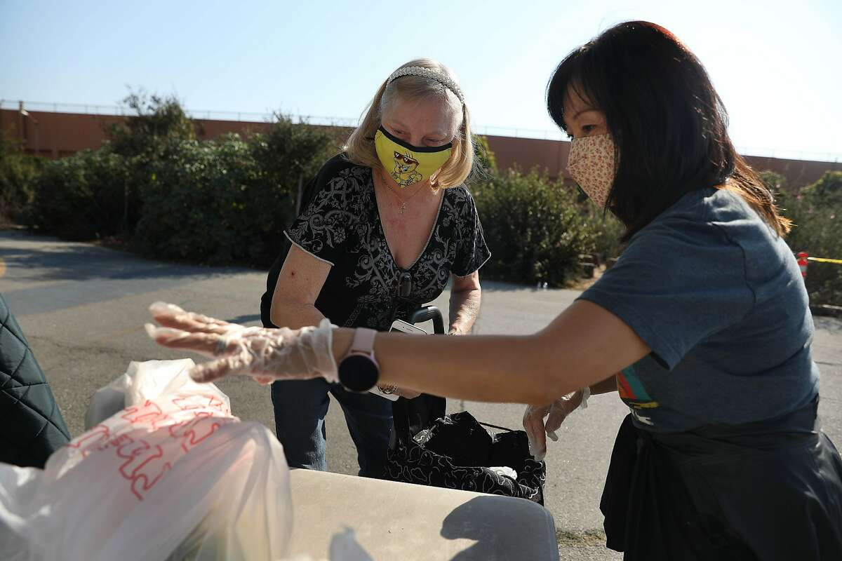 Volunteer Kim Langworthy (right), of San Francisco, assists Vicky Furlong (left) of San Francisco place bags of food into a car at the San Francisco-Marin Food Bank pop-up food pantry at Denman Middle School on Wednesday, October 28, 2020 in San Francisco, Calif.
