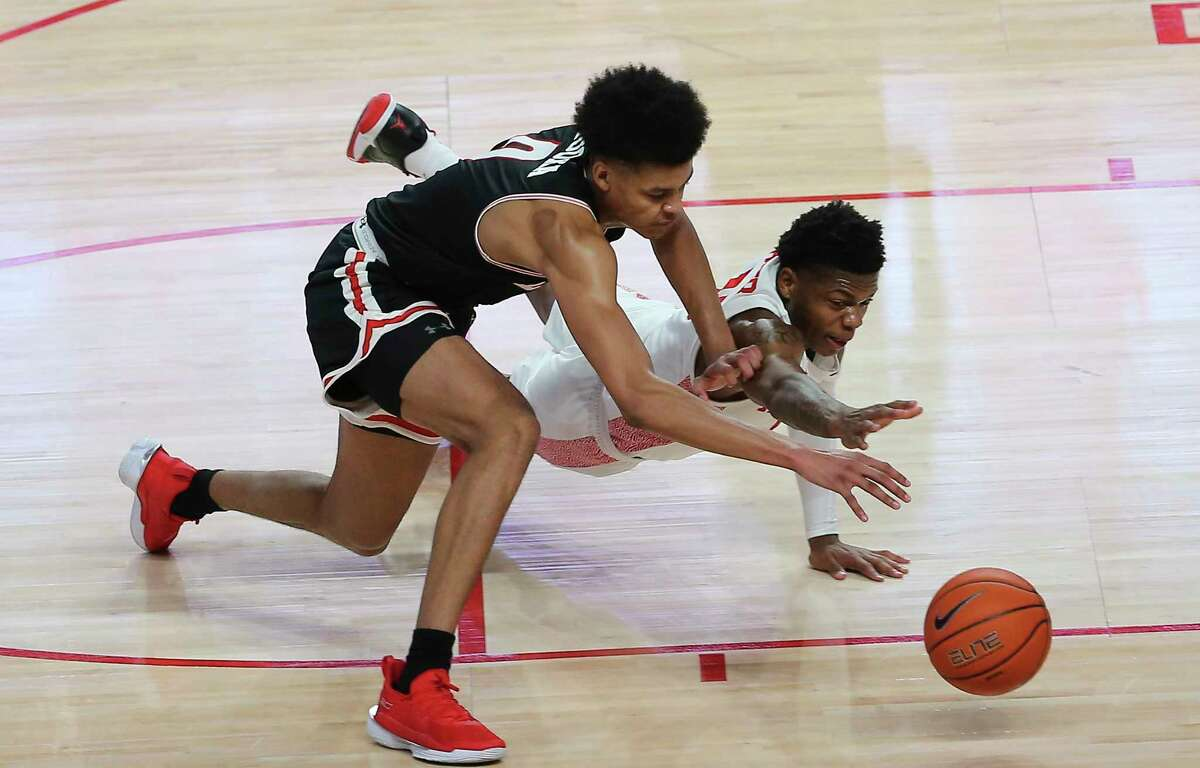 Houston Cougars guard Marcus Sasser (0) and Lamar Cardinals center David Muoka (0) go after a loose ball during the first half of a American Athletic Conference game Wednesday, Nov. 25, 2020, at Fertitta Center in Houston.