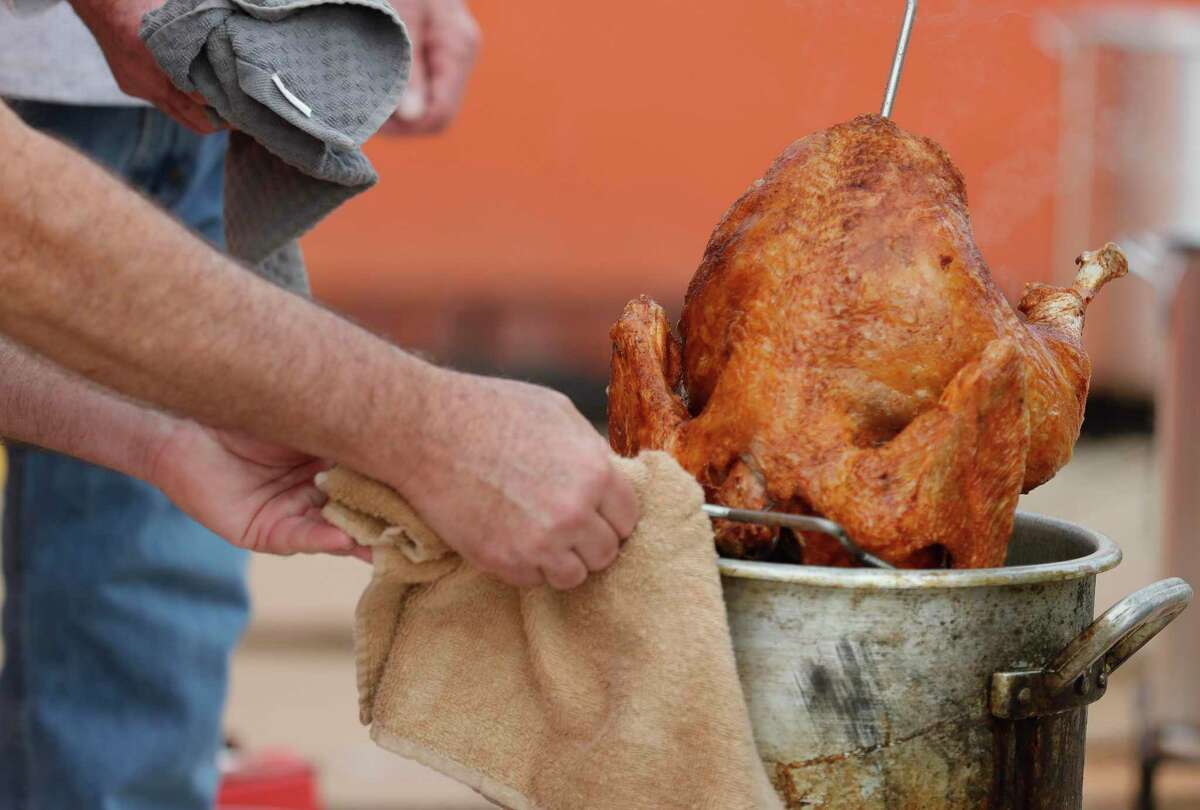 Paul McKelvey takes out a freshly fried turkey at The Abundant Harvest, Wednesday, Nov. 25, 2020, in Spring. Saint Isidore Episcopal Church hosted a turkey fry fundraiser with 30 turkeys and recently opened its cafe to company the organziation's kitchen and food pantry outreach.