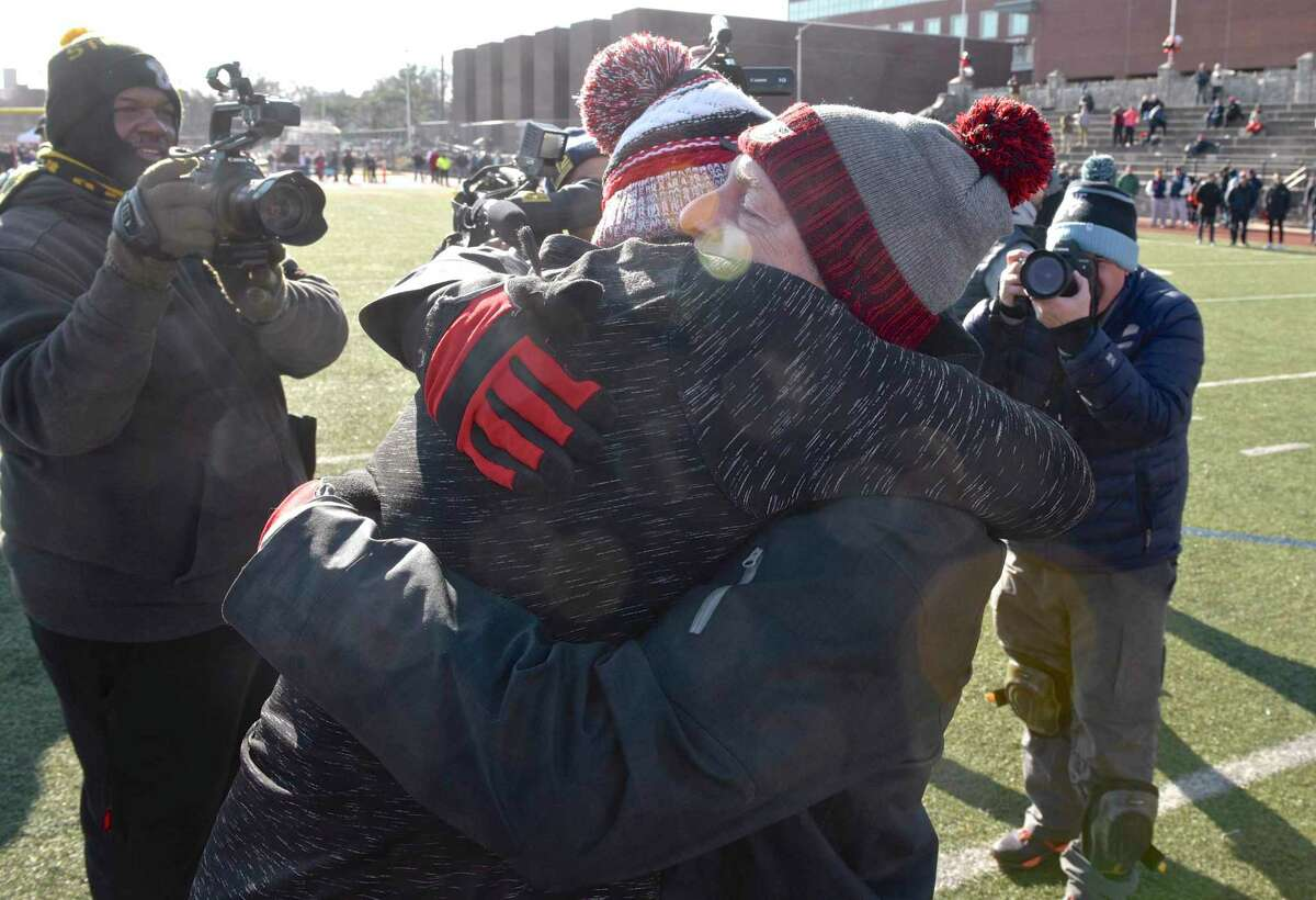Greenwich coach John Marinelli gets a hug from his father, New Canaan coach Lou Marinelli, right, after the Cardinals defeated his father's team in the Class LL championship game on Dec. 8, 2018.