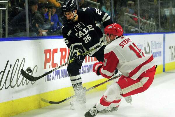 Yale's Phil Kemp passes the puck as Sacred Heart University's Ryan Steele (10) converges during the Connecticut Ice Tournament at the Webster Bank Arena in Bridgeport in January.