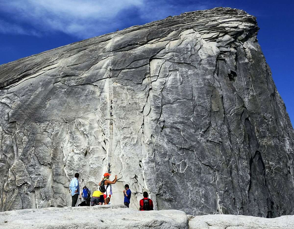 In this July 15, 2014 photo, hikers gather in the foreground as climbers use the assistance of cables to scale Half Dome in Yosemite National Park National Park in California's Sierra Nevada. A hiker fell to his death Monday, May 21, 2018, while climbing the cables in rainy weather, park officials said. NPS spokeswoman Jamie Richards said the man and a companion were scaling the steepest part of the trail where rangers recently installed cables to help hikers get to the top of the 8,800-foot (2,862-meter) rock face. (AP Photo/Brian Melley)