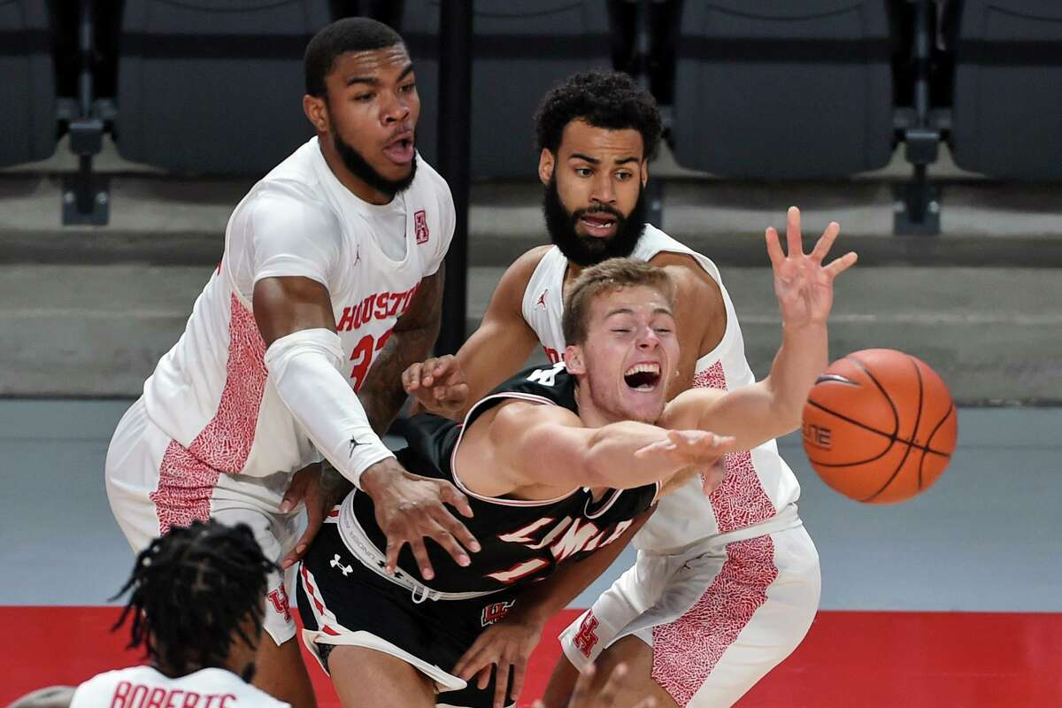 Lamar guard Anderson Kopp, center, passes the ball as Houston forward Reggie Chaney, left, and guard Cameron Tyson defend during the first half of an NCAA college basketball game, Wednesday, Nov. 25, 2020, in Houston. (AP Photo/Eric Christian Smith)
