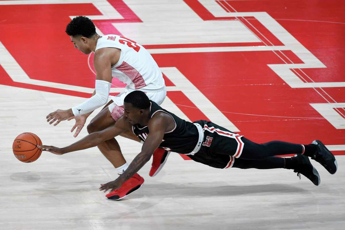 Lamar guard Ellis Jefferson, bottom, and Houston guard Quentin Grimes chase a loose ball during the first half of an NCAA college basketball game, Wednesday, Nov. 25, 2020, in Houston. (AP Photo/Eric Christian Smith)