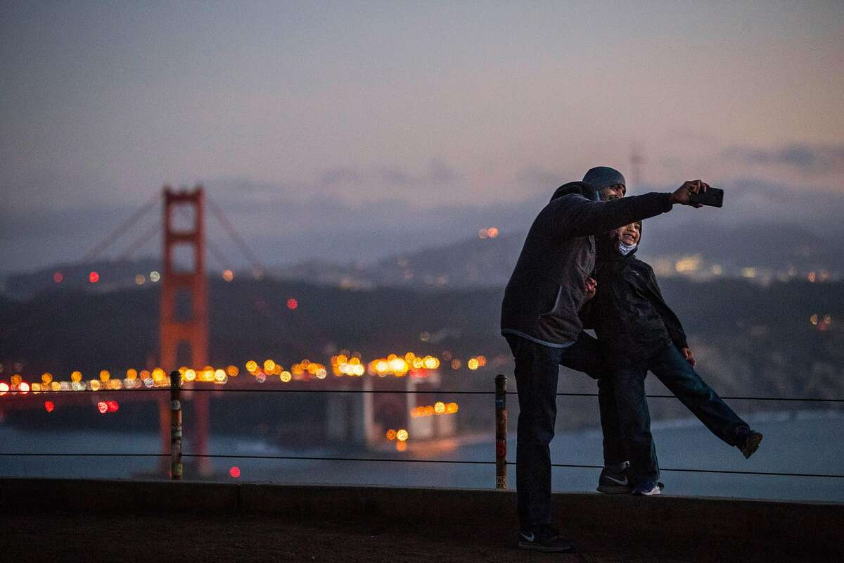 Maneesh Kenia, and his son Evy, 6, of Dublin, pose for a photo on a turnout in the Marin Headlands as they took in some sightseeing un the mild weather in Sausalito, Calif., on Tuesday, November 24, 2020.