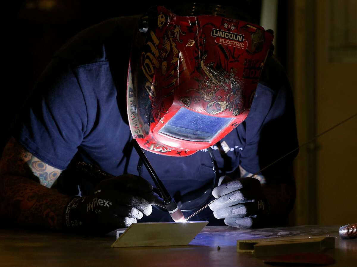 Walter Ayala welds sections for a Thomas Swan sign.