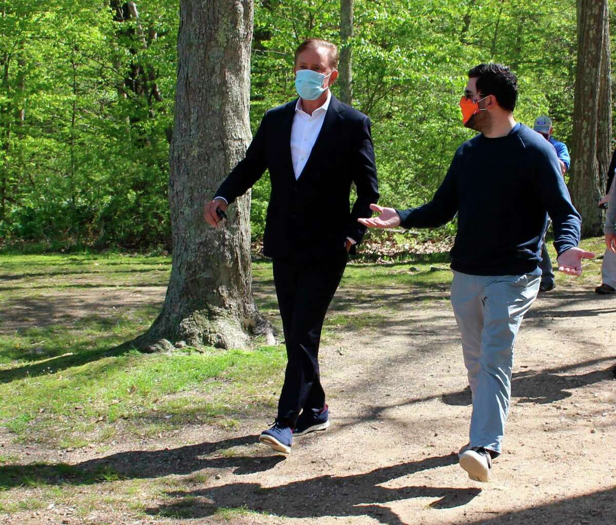 Connecticut Gov. Ned Lamont, left, talks to his communications director, Max Reiss, as they head to a news conference at Gay City State Park in Hebron in May.