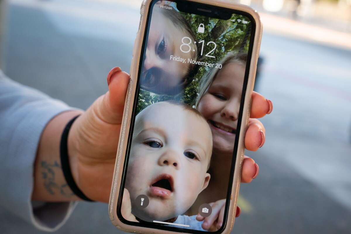 Before starting work at the San Rafael Transit Center, JorDann Crawford shows a cell phone photo of her children: Dustin, 5, Cody, 8 months, and Bella, 9,
